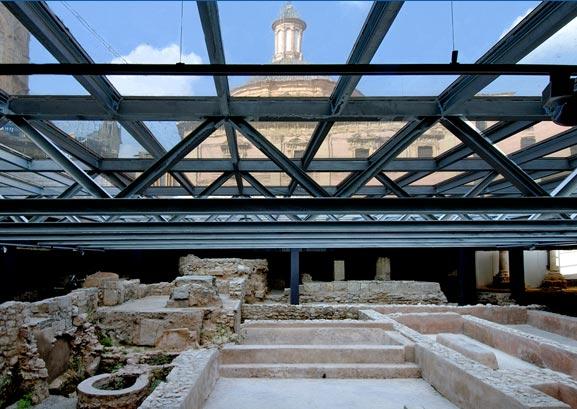 Bajo el suelo acristalado y tras la Basílica, emergen las ruinas de la Valentia romana.
